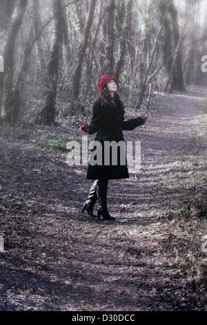 a woman in a black coat with red hat is standing in the woods - Stock Photo