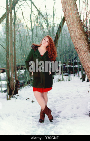 Full-length portrait of beautiful young woman with curly red hair, short red dress, green coat, and bare legs in - Stock Photo