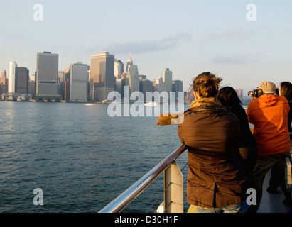 Tourists looking at manhattan from an Ikea bound NYC water taxi. - Stock Photo