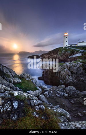 Fanad Head captured as a full moon rises behind the Lighthouse. - Stock Photo