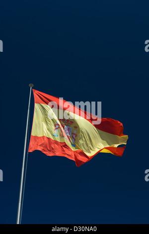 LARGE SPANISH FLAG FLYING ON FLAG POLE WITH BLUE SKY BACKGROUND - Stock Photo