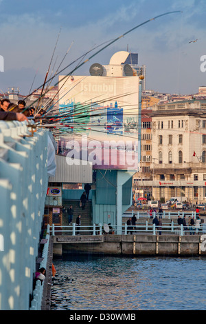 Fishermen and fishing rods on the Galata Bridge with Galata Tower in background, Eminonu Golden Horn Bosphorus Istanbul - Stock Photo