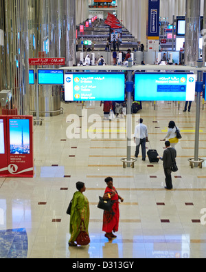Passengers hustle and bustle at the arrival and departure terminal of the Dubai International Airport - Stock Photo
