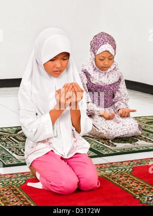 Muslim children praying in Mosque - Stock Photo