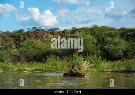 Fisherman paddling a traditional boat on Lake Baringo, Kenya - Stock Photo