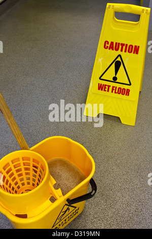 Caution wet floor health and safety sign with mop and bucket - Stock Photo