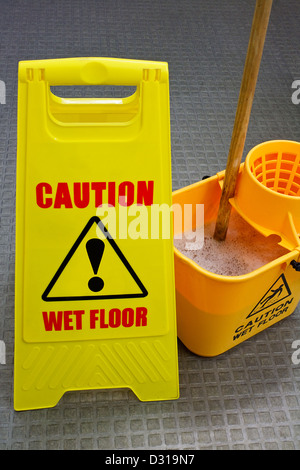 Caution wet floor sign with mop and bucket - Stock Photo