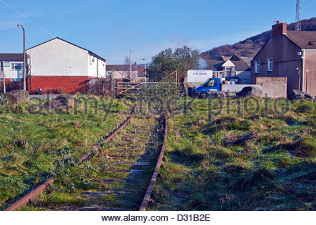 disused railway track and level crossing overgrown with weeds in Briton Ferry near Neath in South Wales - Stock Photo