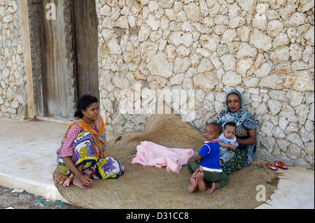 Women and children sitting outside their house, Lamu, Lamu Archipelago, Kenya - Stock Photo