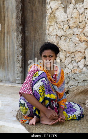 Woman sitting outside her house, Lamu, Lamu Archipelago, Kenya - Stock Photo