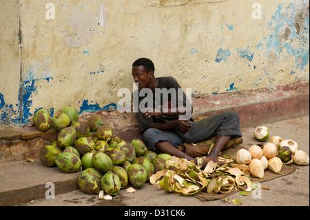 Man selling coconuts for drinking, Lamu, Lamu Archipelago, Kenya - Stock Photo