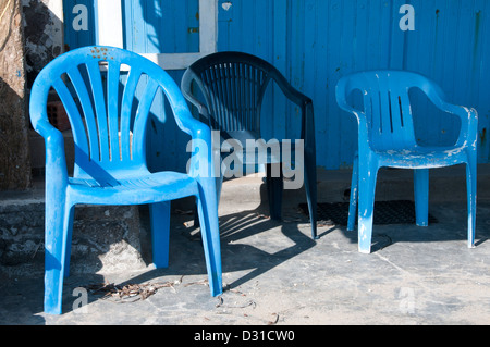 Three blue plastic chairs by a blue door. - Stock Photo