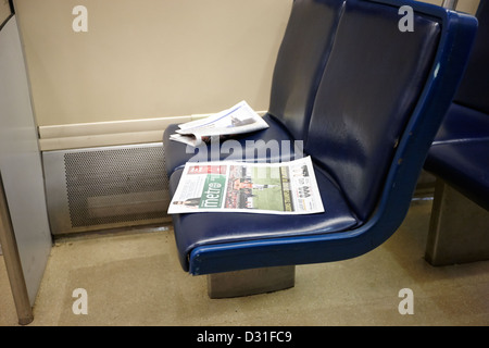 free metro paper discarded on seat on board canada line skytrain Vancouver BC Canada - Stock Photo