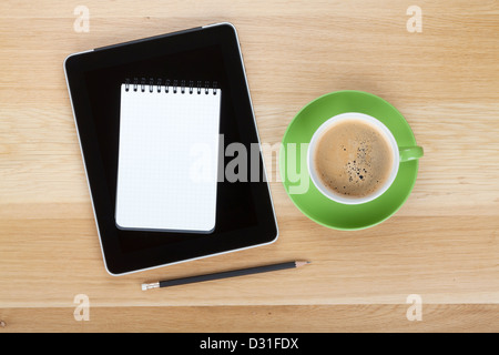 Touch screen tablet computer, notepad, pencil and cup of coffee on wooden table - Stock Photo