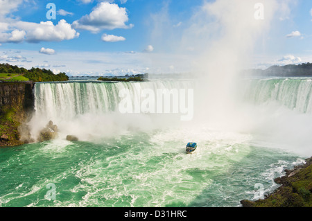 Maid of the mist boat cruise with tourists in blue raincoats Horseshoe falls on the Niagara river Ontario Canada - Stock Photo