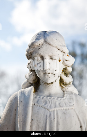 A worn and weathered stone angel bearing moss and lichen on her face. - Stock Photo