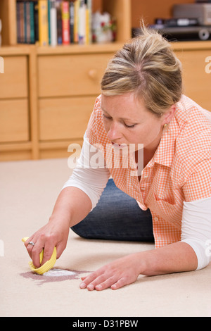 woman cleaning a red wine stain on the carpet with salt stock photo