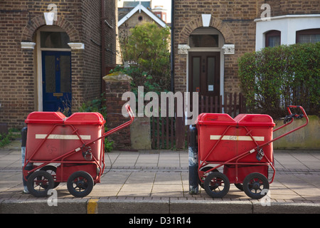 Royal Mail postman trolleys parked on street outside terraced house, England, UK - Stock Photo