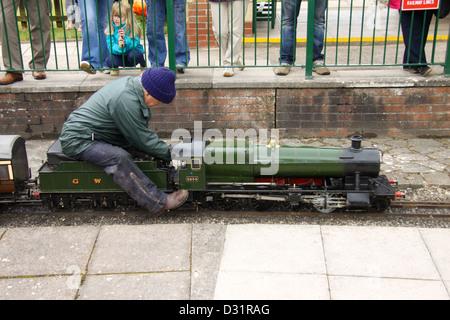 Man driving a miniature 2-8-0 steam locomotive - Stock Photo