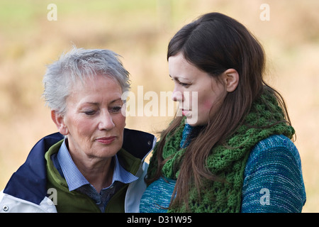 Elderly woman and grown up daughter looking worriedly - Stock Photo