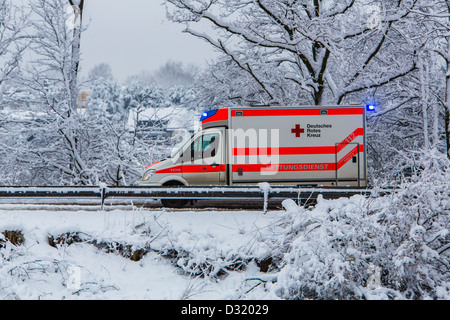 Ambulance of the German Red Cross. At a emergency operation, with lights flashing, on a snowy street in winter - Stock Photo