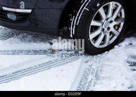 Car with winter tires drives on a road with snow cover. - Stock Photo