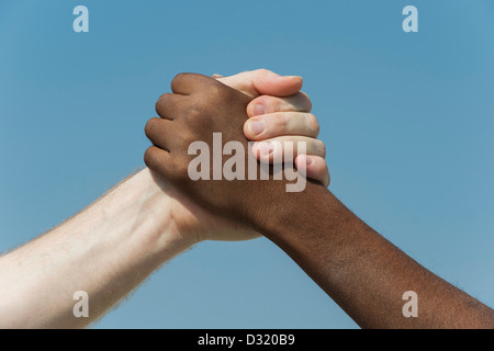 Indian and English hands. Western and Eastern hand shake against a blue sky. india. One humanity concept. - Stock Photo