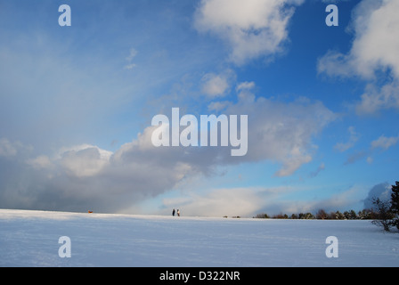 A dramatic gradient of dark and bright blue sky and clouds overlooking a vast covering of snow on a field with people - Stock Photo