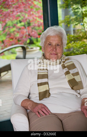Portrait of an older woman sitting in an armchair - Stock Photo