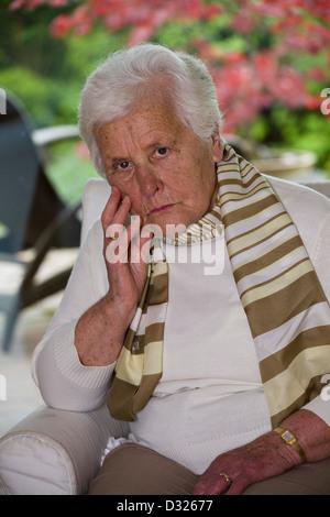 Sad woman sitting in an armchair - Stock Photo