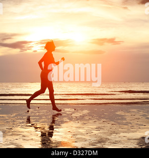 Young woman jogging on the beach at sunset - Stock Photo