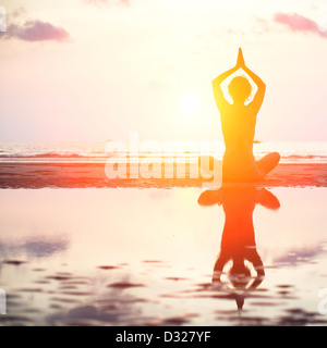 Yoga woman sitting in lotus pose on the beach during sunset, with reflection in water (in bright colors) - Stock Photo