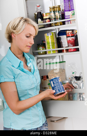 Woman checking best-before date - Stock Photo