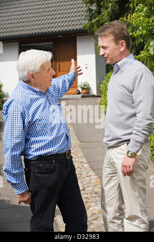 Father and son discussing in front of residence - Stock Photo