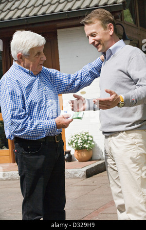 Father handing money to his son - Stock Photo
