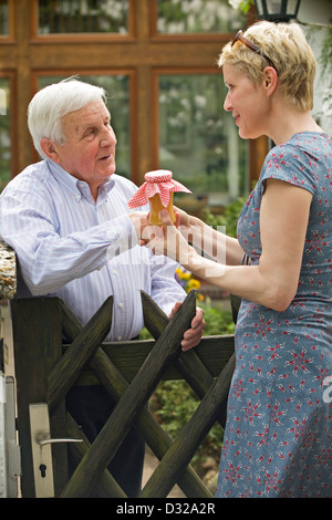 Woman giving gift to the neighbor - Stock Photo