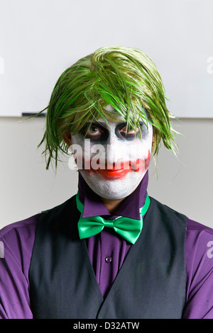 Young man dressed up like The Joker with crazy green hair very messy makeup wearing small green bow tie, purple - Stock Photo
