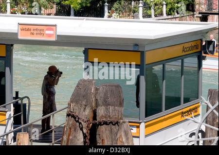 A tourist taking a picture on the Accademia vaporetto (water-bus) stop, Dorsoduro, Venice, Italy. - Stock Photo