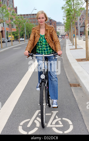 Female biker cycling on the left side of the street - Stock Photo