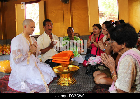 A young novice monk at his initiation ceremony receiving blessing and prayers from his family wearing white traditional - Stock Photo