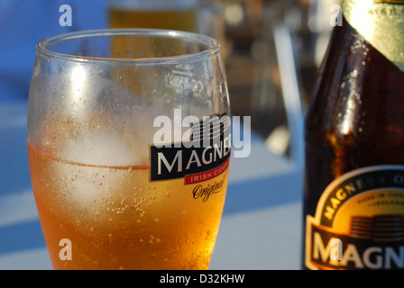 cold refreshing alcoholic beverage on a white outdoor bar table at a holiday resort in the hot sun covered in condensation - Stock Photo