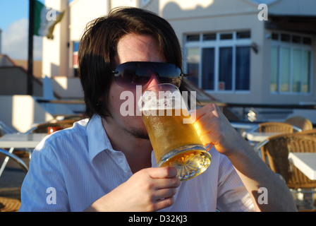 A man drinking a cold refreshing alcoholic beverages on a white outdoor bar table at a holiday resort bar in the - Stock Photo