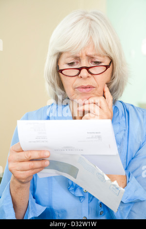 Elderly lady reading an official letter - Stock Photo