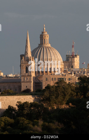 Valletta, St. John`s Co Cathedral, evening sun, trees in foreground, blue/grey sky, wintry - Stock Photo