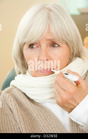 Elderly lady with clinical thermometer - Stock Photo