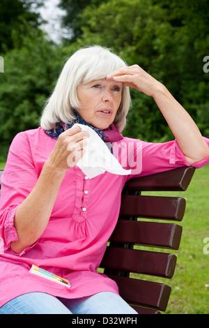 Elderly lady suffering from summer minor illness - Stock Photo