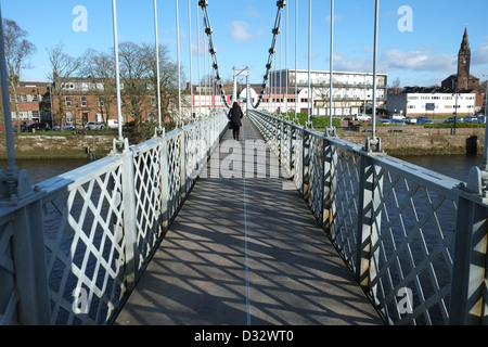 A woman in red scarf walks across the River Nith suspension bridge,Dumfries, Scotland. Far right is St Michaels, - Stock Photo
