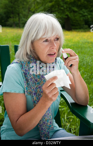 Elderly lady suffering from hay fever - Stock Photo
