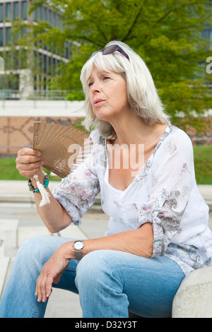 Sweating lady fanning herself - Stock Photo