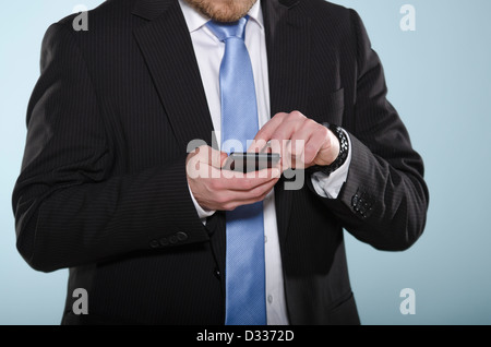 Businessman using smartphone. Middle section of casually suited man using a touch screen phone with his finger. - Stock Photo